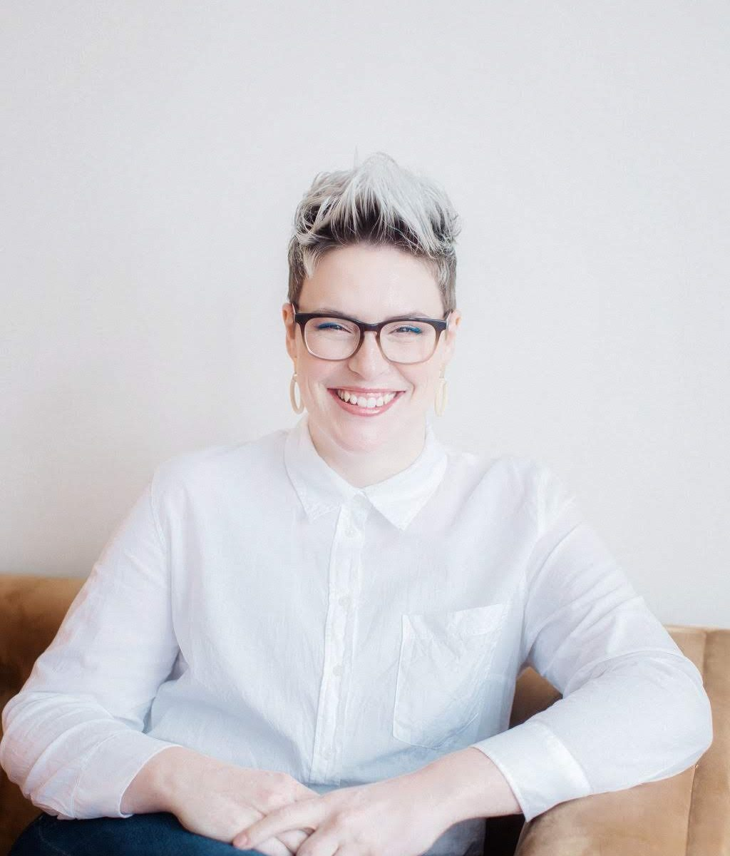 Erin Neilson, calligrapher, sitting and smiling on a couch